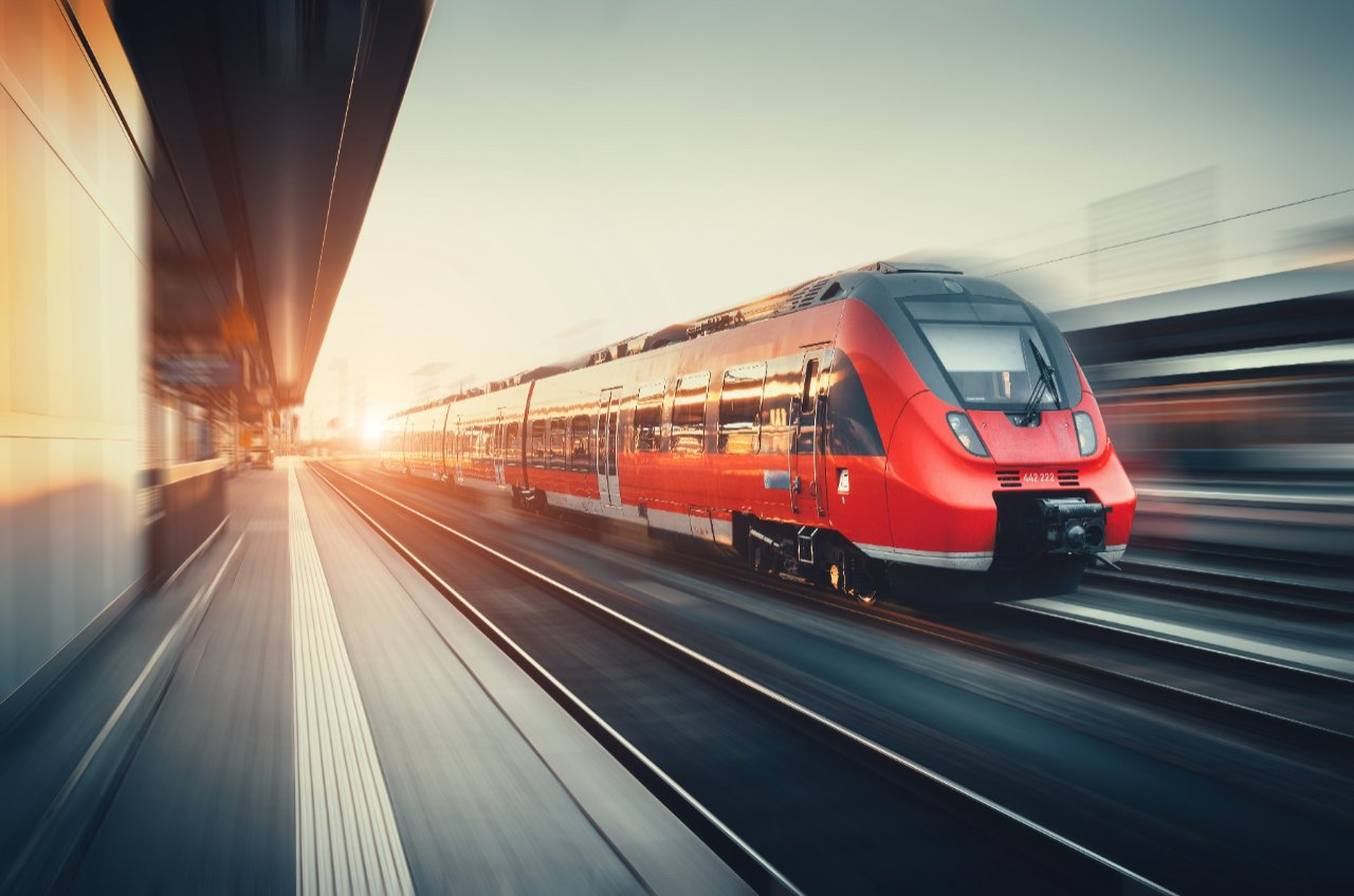 Beautiful railway station with modern high speed red commuter train with motion blur effect at colorful sunset in Nuremberg, Germany. Railroad with vintage toning