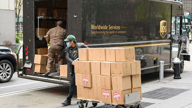 workers working in retail industry loading packages on delivery trucks
